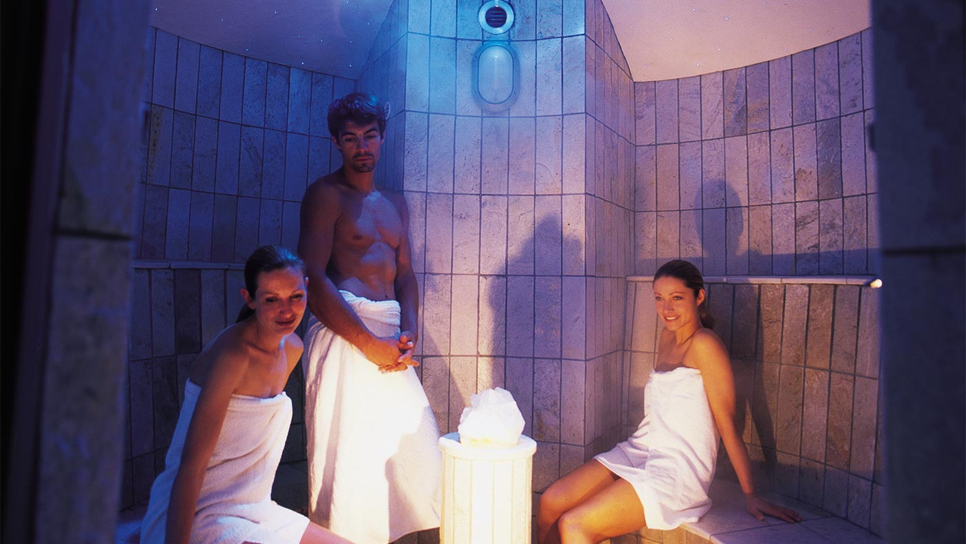 Two ladies and a man relax in the steam bath of Acquafun in San Candido