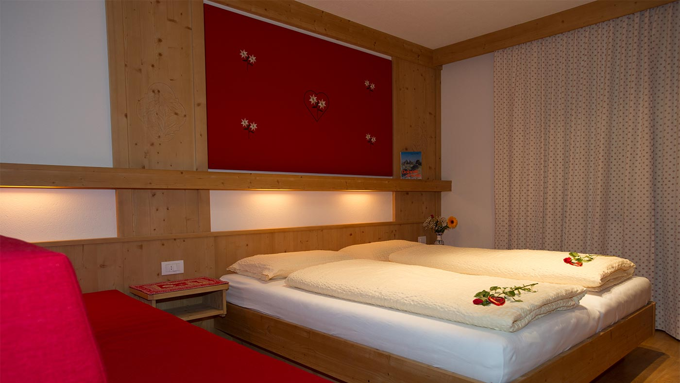 The romantic bed of a wooden double room in the Residence Edelweiss - two red roses on the bed