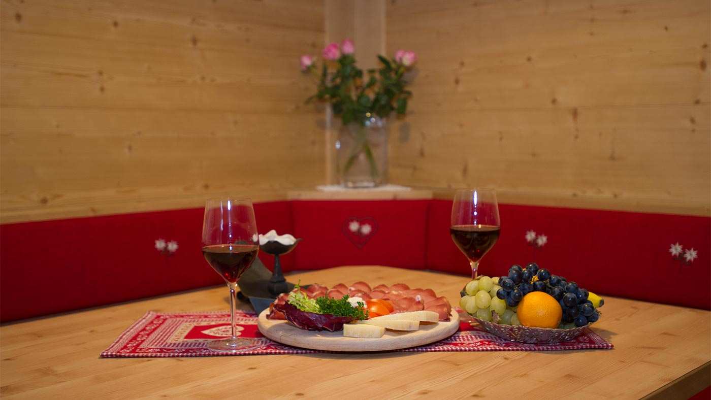 'Marend' at the Residence Edelweiss - a cutting board with a glass of wine and fresh fruit on the table