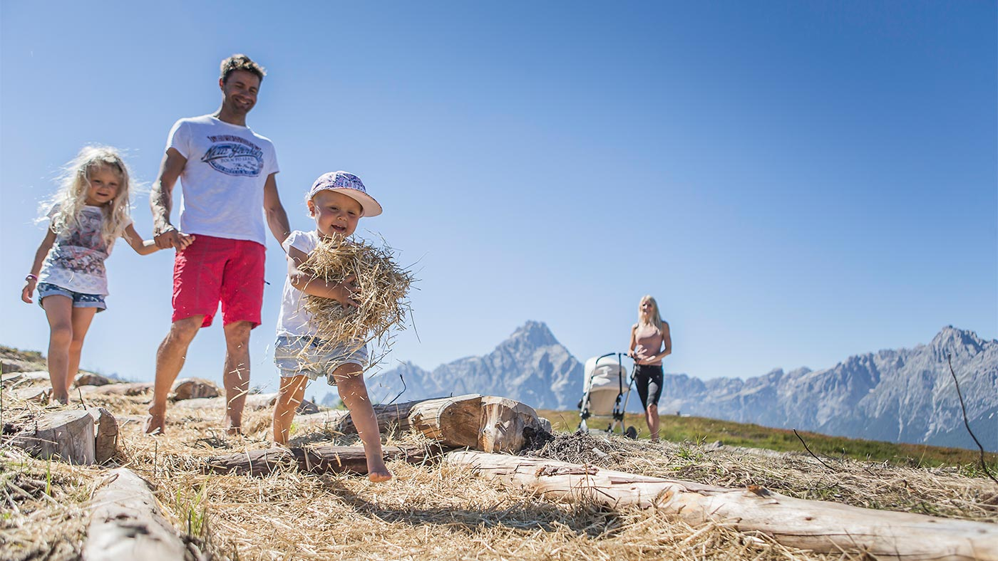 A young family gathering hay in San Candido