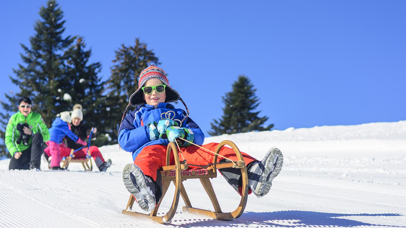 Sledge slope in San Candido, in the foreground - a child sits with sunglasses on his sledge